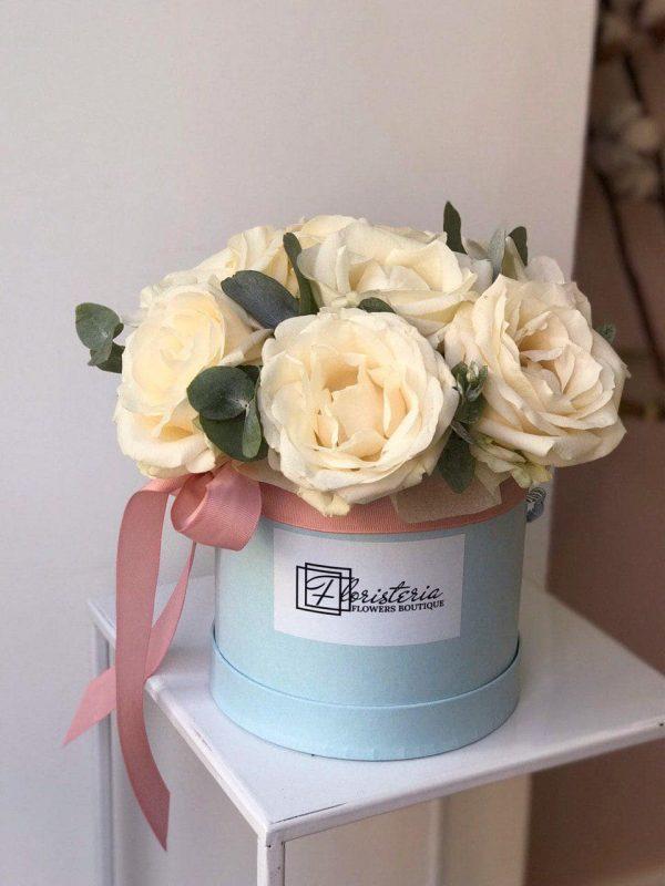 Niebieskie pudełko z 10 kremowych róż oraz eukaliptusa