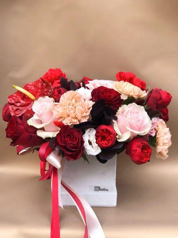 Kwadratowe szare pudełko w rozmiarze M w bordowych odcieniach z mixem goździków, róż, eustomy, leukadendrona oraz anturiuma