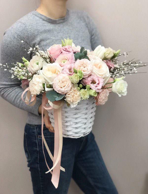 Kosz wypełniony kwiatami w pastelowej kolorystyce
